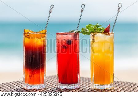 Close-up Of Set Of Three Refreshing Fruit Cocktails Standing On Table On Beach, Blurred Turquoise Se