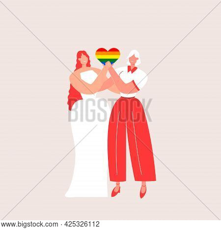 Happy Lesbian Couple Wedding. Two Lesbians In Wedding Dresses Hug And Hold A Heart Decorated In The