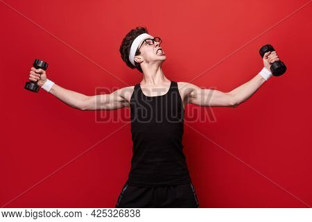 Comic Geek Young Male Nerd In Sportswear And Glasses Doing Bodybuilding Exercise With Dumbbells Agai