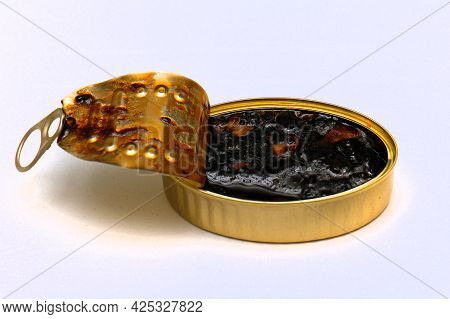 Open Gold Metal Can With Chopped Squids In Black Ink Sauce On White Background