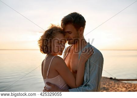 Beautiful Young Caucasian Lovers Hugging Each Other While Dating On Beach At Sunset. Romantic Date C