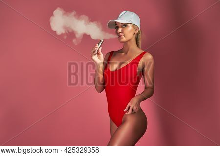 Young Sexy Woman In Red Swimsuit And Cap Is Vaping, Posing On Studio Pink Background. A Cloud Of Vap