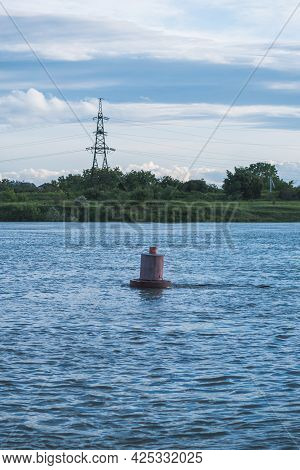 Red Navigation Buoy In The River. Against The Background Of Grass, Forest And Power Line Towers. Blu