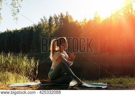 Yoga And Meditation In Nature. Sporty Young Woman Meditating At Sunset Or Sunrise, Outdoors. Yogi Gi