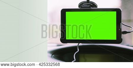 Navigator On The Windshield Of The Car. Gps Navigation Device In The Car. Background With Copy Space