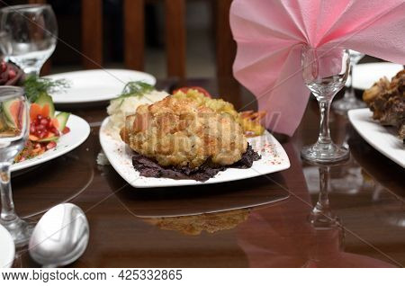 Kiev Cutlet Made Of Meat Fried In Breadcrumbs With A Side Dish Of Rice Is On The Banquet Table