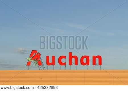Poland, Warsaw - June 02, 2021: Auchan Advertising Sign On The Roof Of The Hypermarket. Auchan Super
