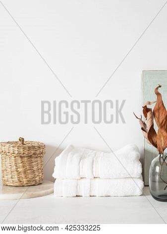 White Bath Background Front View With Glass Vase, White Towels And Decor On White Shelf And Wall. Fr