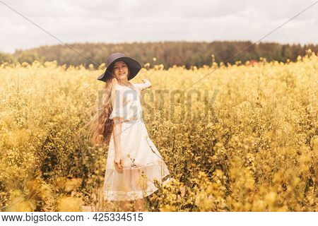 A Young Happy Girl Enjoys Nature On The Field Of Blossoming Canola. The Corcept Of Youth And Freedom