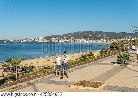 Palma De Mallorca, Spain; June 25 2021: Elderly Couple Walking With A Face Mask Along The Promenade