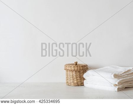 Wicker Straw Box And White Towels On White Background. Front View. Minimal Bath Background. Copy Spa