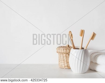 Minimal Bath Background With Bamboo Toothbrushs In Ceramic Glass, Wicker Box And White Towels On Whi