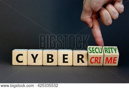 Cyber-security Vs Cybercrime Symbol. Businessman Turns Wooden Cubes, Changes Words Cybercrime To Cyb