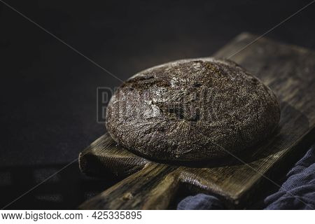 Homemade Rye Bread On A Wooden Board, On A Dark Background. Fresh Sourdough Bread On Black Backgroun