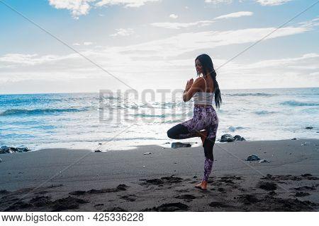 Life Balance. Full Length Of Slim Sporty Woman In Sports Wear Doing Tree Pose Or Vrikshasana While P