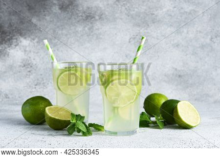 Iced Tea With Lime. Cold Lemonade With Lime On A Concrete Background.