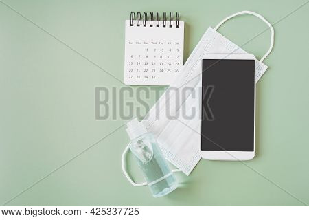 Smart Phone With Clipping Path On Touchscreen On Face Mask, Bottle Of Alcohol Gel And Opened Calenda