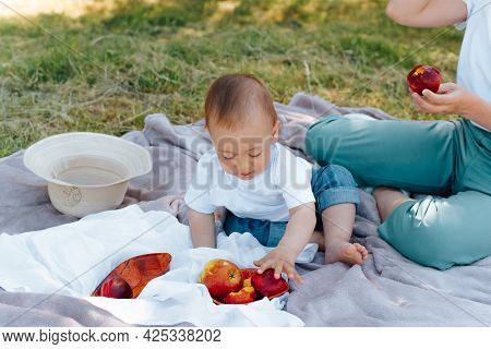 Baby On Picnic, Outdoors. Little Cute Child With Mommy Eats Fruit While Sitting On A Blanket On The