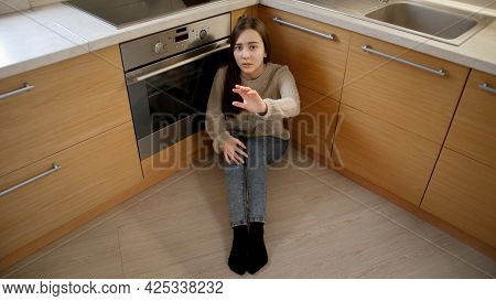 Afraid Teenage Girl Hiding Face In Hands And Crying Because Of Angry Parent Moving Towards Her. Conc