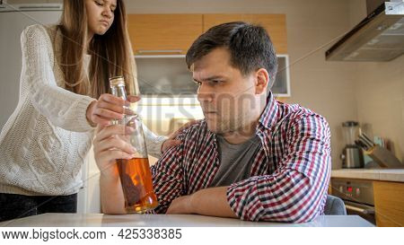 Angry Teenage Girl Taking Away Bottle Of Alcohol From Her Drunk Father Drinking On Kitchen. Alcoholi