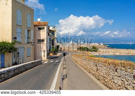 Pedestrian walkway and narrow urban road along houses and Mediterranean sea coast under blue sky in Antibes - city on French Riviera.