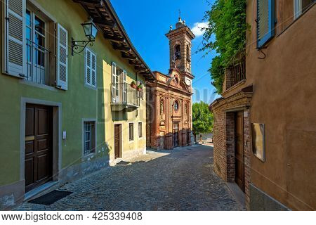 Narrow cobblestone street among houses and old brick church under blue sky in Piedmont, Northern Italy.