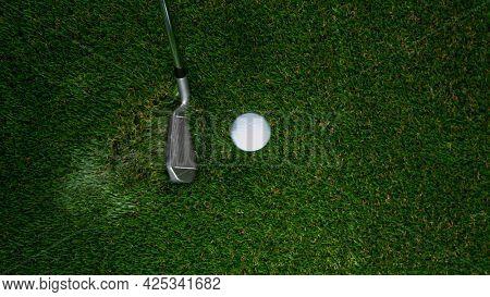 Golf club hitting golf ball on green grass.