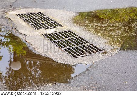 Flooding Drainage System With A Hatch Grate For Drainage Of Rainwater On The Wet Road With Puddles A