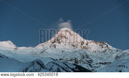 Stepantsminda, Gergeti, Georgia. Peak Of Mount Kazbek Covered Snow And Famous Gergeti Trinity Tsmind