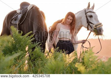 Smiling Woman Walking Her Two Horses, Holding Them By The Bridle. Animals Chew Fresh Grass In The Me