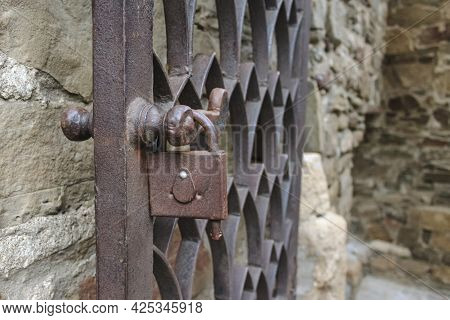 An Old Rusty Metal Wrought-iron Door With A Padlock On The Background Of A Stone Wall