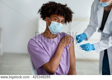 Medical Doctor Or Nurse Giving Coronavirus Vaccine Shot To Black Teenage Guy At Clinic