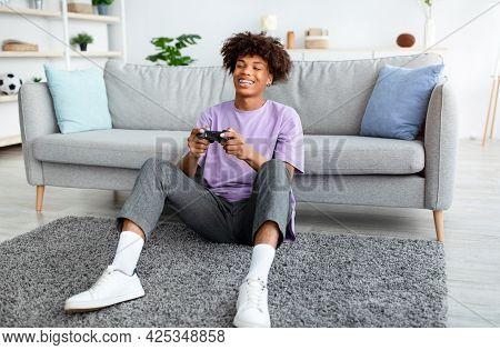 Happy Black Teenager Enjoying Videogame On Playstation, Having Fun At Home, Full Length