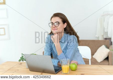 A Pensive Young Woman Sits In The Kitchen And Thinks About Solving A Work Problem. Thoughtful Young