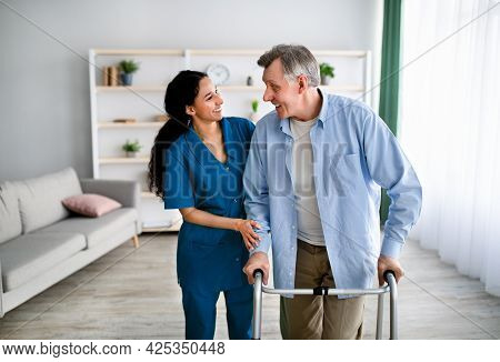 Female Caregiver Assisting Elderly Man To Walk With Frame At Home. Professional Health Care Service
