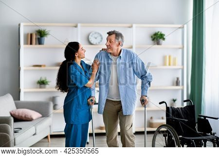 Female Nurse Helping Elderly Male To Walk With Crutches At Home. Professional Medical Care For Disab