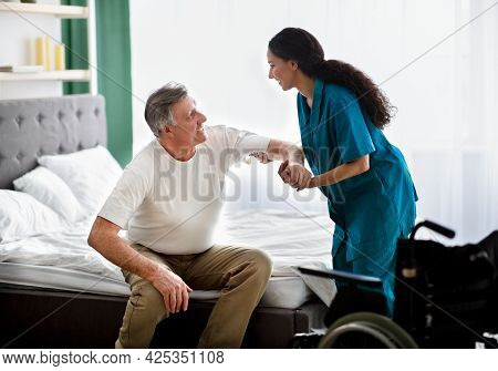 Caregiver Helping Elderly Male To Get Into Wheelchair At Home. Rehabilitation And Medical Care For D