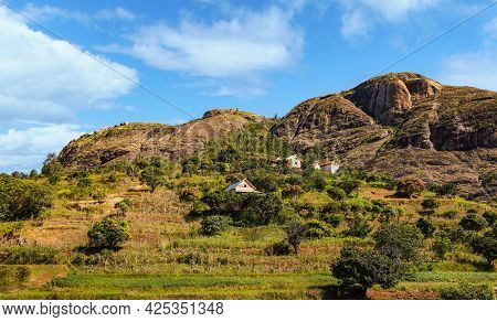 Typical Madagascar Landscape - Green And Yellow Rice Terrace Fields On Small Hills With Clay Houses