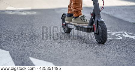 Young Man In Casual Trousers Riding An Electric Scooter Detail On His Feet And Wheel Over Asphalt Ro