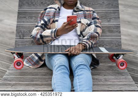 Young African Girl Sit In Skate Park And Chat In Mobile Phone. Closeup Of Black Casual Skater Woman