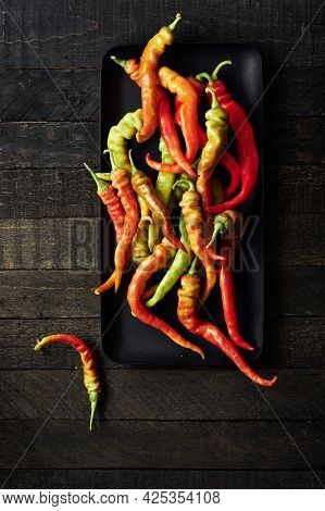 Fresh Red Peppers On A Dark Wooden Background.