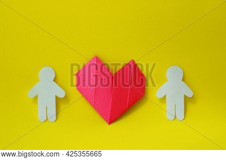 Two Silhouettes Of People Are Carved From White Paper With Origami Heart Between Them On A Yellow Ba