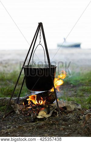 Tourist Pot Hanging Over The Fire On A Tripod. Cooking In The Campaign.