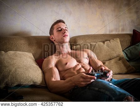 Young Shirtless Man Playinig Videogame On Smartphone At Home
