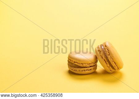 Lemon flavor French macaron cookies closeup on background of the same pastel yellow colour with copy space