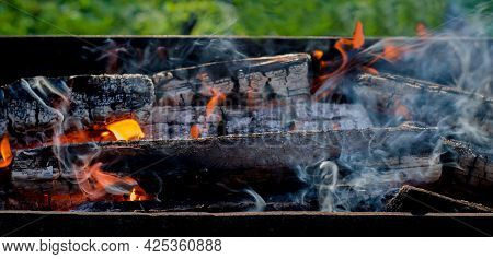 Burning Wood In A Barbecue Grill. Open Fire, Flames, Smoke From Burning Firewood In Nature