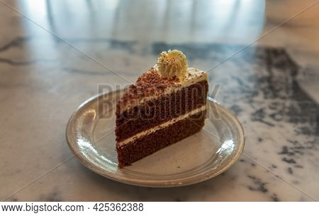Slice Of Delicious Coffee Cake With Butter Cream Slice In Ceramic Plate On The Marble Table. Sweet O