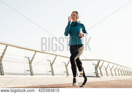 Young healthy sportswoman with prosthetic leg exercising running outdoors wearing headphone