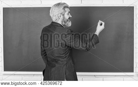 Every Lesson Changes Person. Bearded Man Write On Chalkboard. Senior Teacher Give Lesson. Homework A