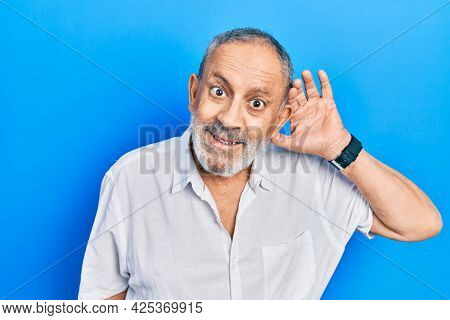 Handsome senior man with beard wearing casual white shirt smiling with hand over ear listening an hearing to rumor or gossip. deafness concept.
